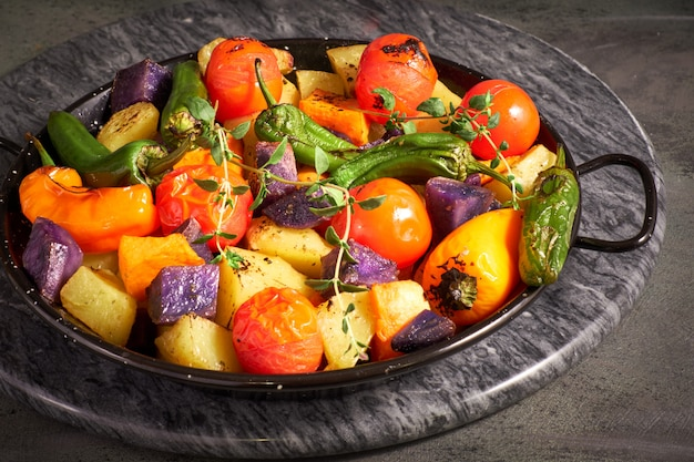 Деревенские, запеченные в духовке овощи в форме для выпечки. сезонная вегетарианская еда на темной каменной доске Premium Фотографии