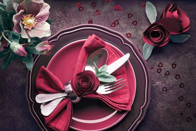 バラとアネモネで飾られたバージンディプレートと食器、クリスマスまたはバレンタインディナーのセットアップを備えたフラットレイアウト Premium写真