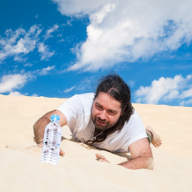 Жаждущий человек в пустыне тянется к воде Premium Фотографии
