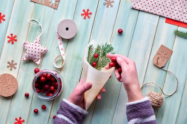 さまざまなクリスマスまたは新年の冬休みの環境に優しい装飾、クラフト紙パッケージ、再利用可能な、または廃棄物ゼロのギフト。フラットは木の板、緑の葉と合板の円錐形のクランベリーに横たわっていた。 Premium写真
