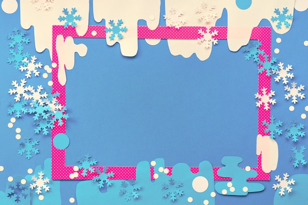 ペーパークラフト、コピースペース付きの平面図。紙の雪とさまざまな雪のピンクまたはマゼンタのフレーム。青、ピンク、白の創造的なクリスマスや新年の紙の背景。 Premium写真