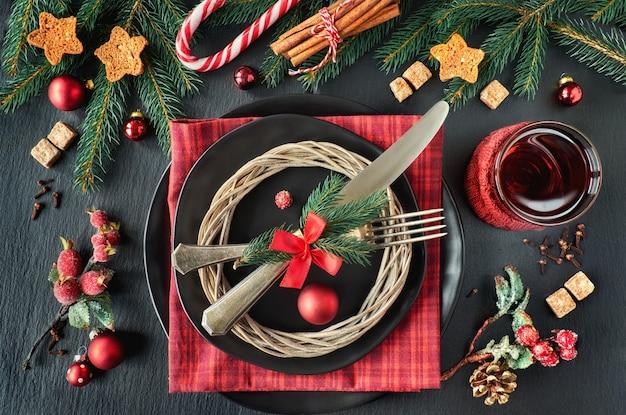 Черные тарелки и винтажные столовые приборы с елочными украшениями зеленого, красного и оранжевого цвета Premium Фотографии