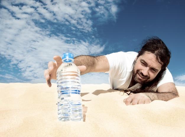 Жаждущий человек тянется к бутылке воды Premium Фотографии