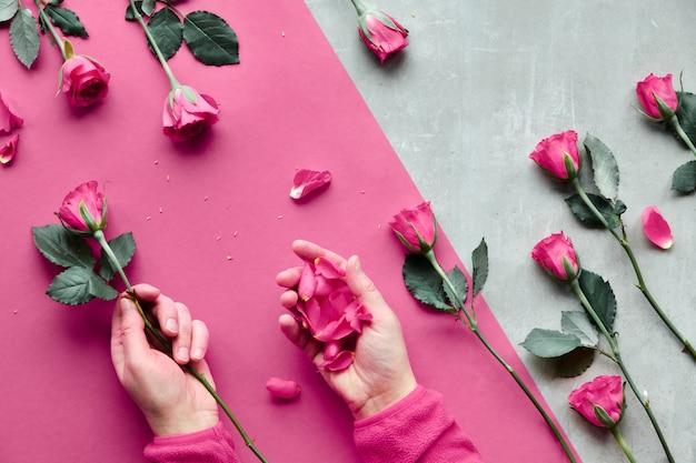 石の斜めの幾何学的な紙。ピンクのバラと花びらを保持している女性の手でフラットを置きます。挨拶の概念バレンタインの日、誕生日、母の日または他の小さな機会の平面図。 Premium写真