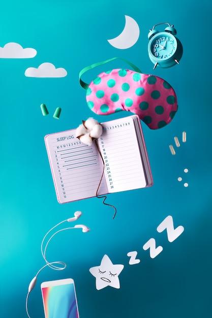 睡眠ログ手書き日記で健康的な夜睡眠の創造的なコンセプト。睡眠マスク、目覚まし時計、イヤホン、耳栓、丸薬の飛行または空中浮揚。 Premium写真