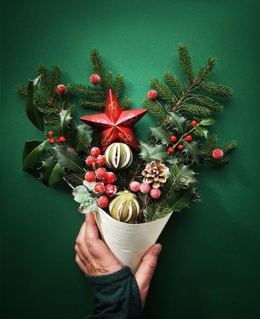 Елочные украшения, еловые веточки, ягоды, падуб, сухой лайм и звезда в конусе, держась за руки, плоская планировка Premium Фотографии