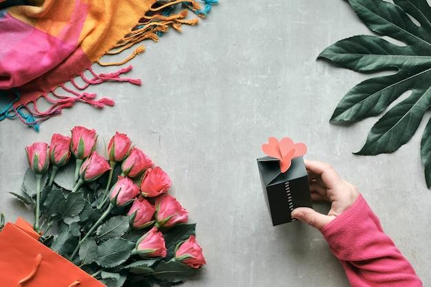 フラットレイアウト、バラの花とエキゾチックな植物の葉の束のある静物。手は、上に心で小さなギフトボックスを保持しています。明るい石のトップビュー。バレンタイン、誕生日または母の日の概念。 Premium写真