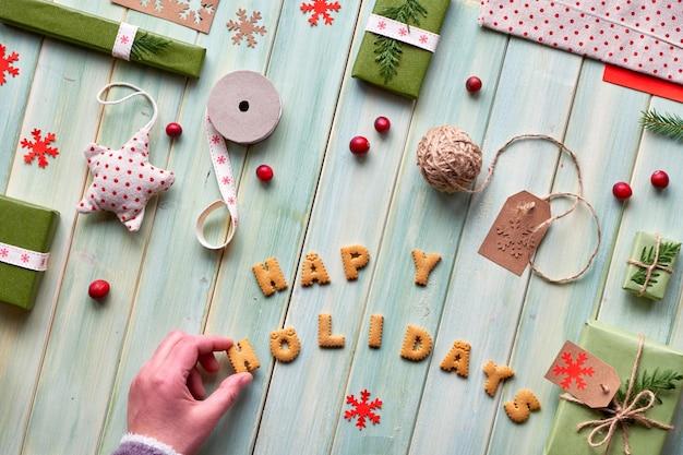 Различные рождественские или новогодние зимние праздничные экологичные декорации, крафт-бумажные пакеты и различные безотходные подарки. квартира лежала на зеленом дереве, рука и текст «счастливого рождества» из печенья. Premium Фотографии