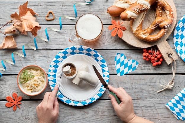 Октоберфест традиционная еда и пиво, плоско лежал на деревянном столе Premium Фотографии