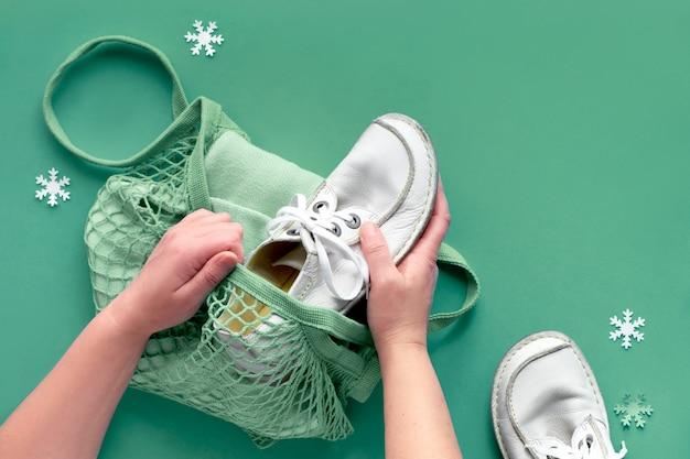 靴と服をメッシュバッグに梱包の手でコンセプトフラットを置きます。寄付のドライブに参加して、火曜日に商品を贈ります。不要な商品を収集し、それを必要としている人に渡します。 Premium写真
