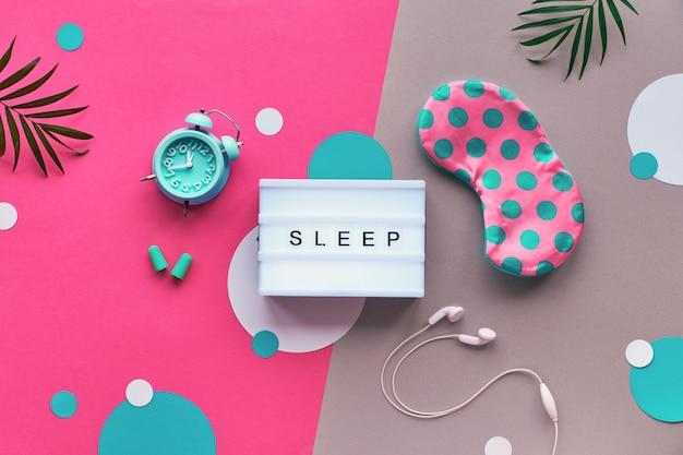 Плоская планировка, лайтбокс с надписью «спи». здоровый ночной сон творческая концепция. спящая маска, синяя мята, сигнализация, наушники, беруши. двухцветная розовая серебряная стена с бумажными кругами и листьями. Premium Фотографии