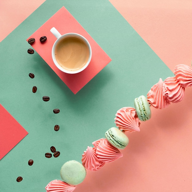 コーヒーとお菓子のミントとサンゴ色の幾何学的な紙の壁 Premium写真