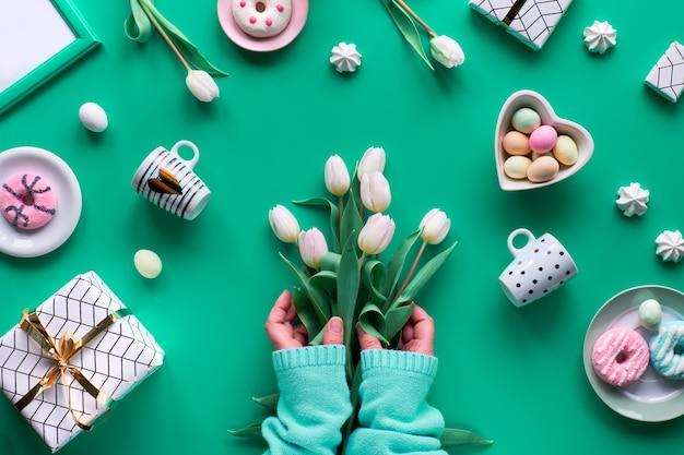Геометрическая весна плоской лежит на фоне зеленой мяты. пасха, день матери, весенний день рождения или юбилей в деревенском стиле. рука с белыми тюльпанами. пасхальные яйца, кофейные чашки, свежие тюльпаны и пончики. Premium Фотографии