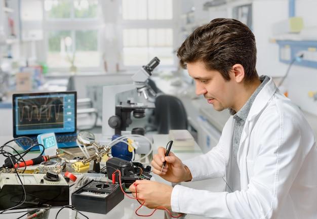 Молодой мужской техник или инженер ремонтирует электронное оборудование Premium Фотографии