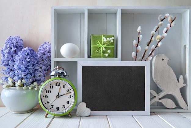 古い目覚まし時計、青いヒヤシンスの花、さまざまなオブジェクトのディスプレイキャビネット。黒板にチョークテキスト「春」 Premium写真