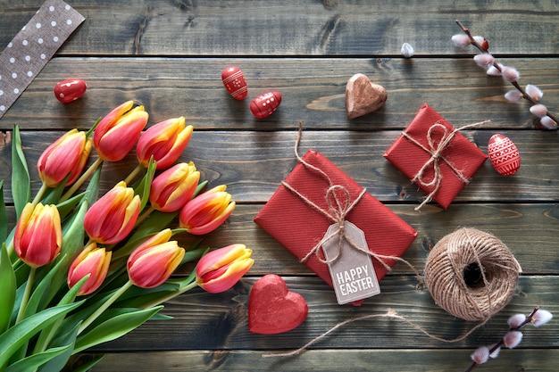 イースターアレンジメント:赤いチューリップ、包まれた贈り物、コード、装飾的なハート Premium写真