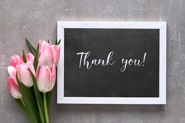 黒板にピンクのストライプの白いチューリップのテキスト「ありがとう」の挨拶、灰色の石の上に平らに置く Premium写真