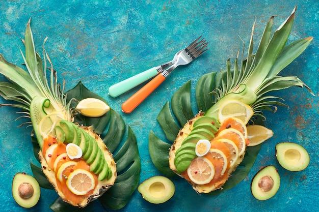 レモンとウズラの卵とスモークサーモンとアボカドのスライスとパイナップルボートの平面図、フラットテクスチャ背景に置く Premium写真