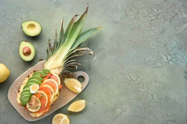 スモークサーモン、アボカド、レモン、ウズラの卵とパイナップルボートのトップビュー Premium写真