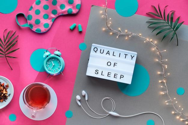 Маска для сна, будильник, наушники и беруши. успокаивающие средства - таблетки, капсулы и чай. плоский макет, двухцветный розовый и крафт-бумага текст Premium Фотографии
