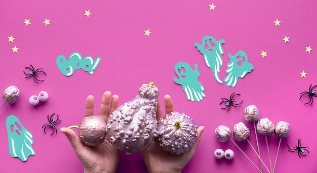 Творческая квартира хэллоуина лежала на фиолетовом бумажном фоне с бумажными призраками, звездами и шоколадными глазами. руки в черных сетчатых перчатках Premium Фотографии