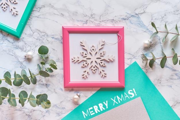 幾何学的なクリスマスフラット横たわっていたピンクと緑のフレームのトップビュー。新鮮なユーカリの小枝とピンクのフレームの装飾的な白い輝くスノーフレーク。 Premium写真