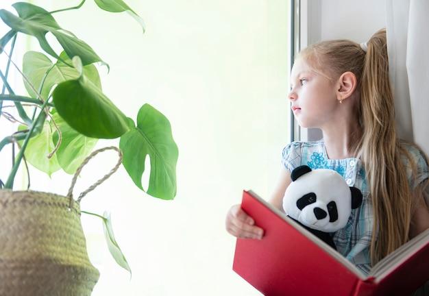 Грустная девочка у окна Premium Фотографии