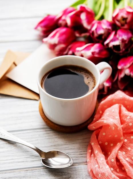 一杯のコーヒーとピンクのチューリップ Premium写真