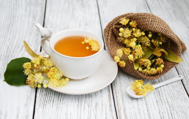 シナノキの花とハーブティーのカップ Premium写真
