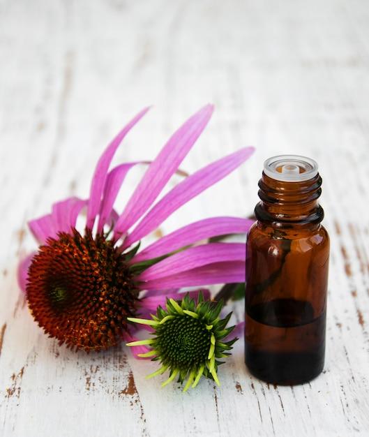 Бутылка с эфирным маслом с фиолетовой эхинацеей Premium Фотографии