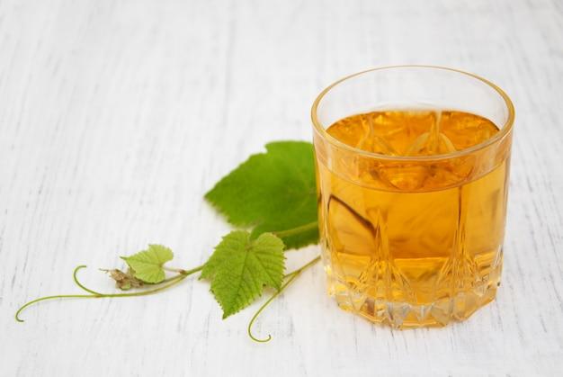 ワインと白ブドウの葉を持つガラス Premium写真