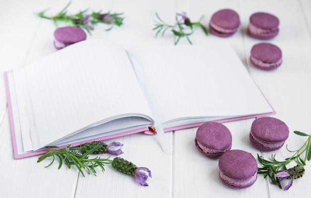 フランスのマカロン、きれいなノートとラベンダーの花 Premium写真