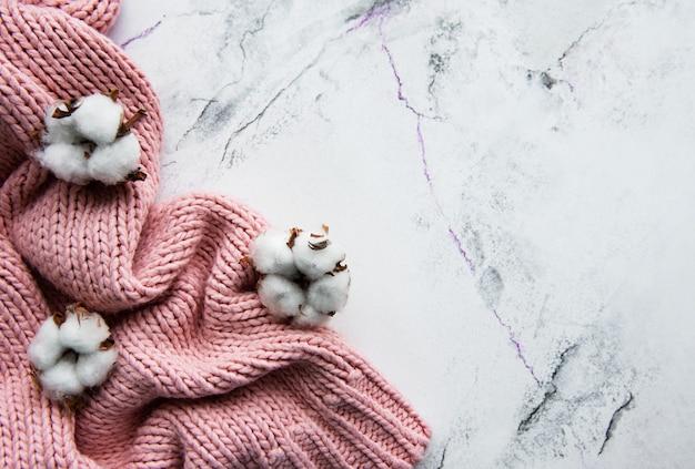 ピンクのニットセーターとコットンの花 Premium写真