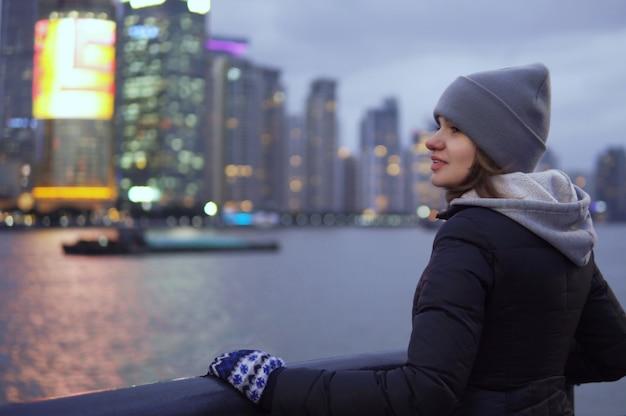 Молодая девушка в черном пиджаке и шляпе смотрит на достопримечательности шанхая на набережной вайтана Premium Фотографии