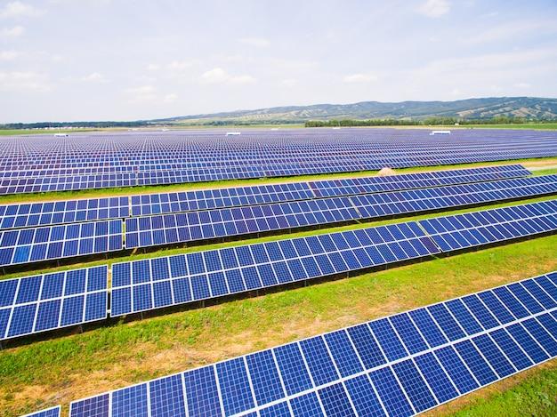 青い空と緑の芝生の上の太陽電池パネルのクローズアップ。 Premium写真