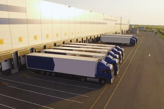 Распределительный склад с грузовиками, ожидающими погрузки Premium Фотографии