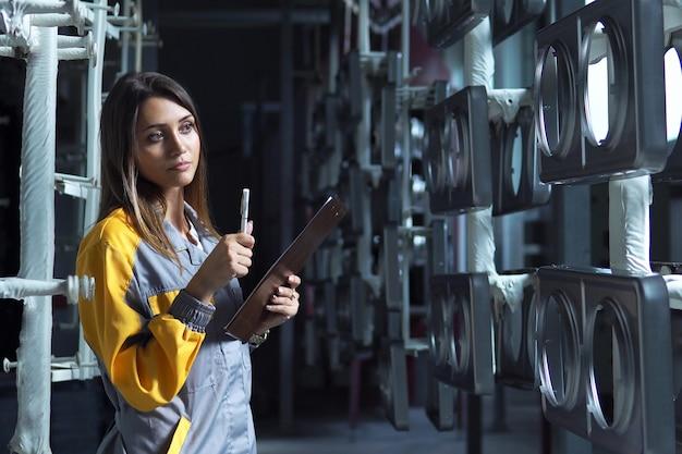 若いきれいな白人女性が工場の塗装工場で働いており、未塗装の金属製品をチェックし、チェックリストに記録を残しています。 Premium写真