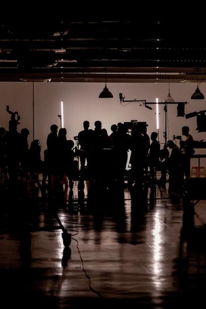 Силуэт сцены видеопродукции за кадром, команда лайтман и оператор работают вместе с режиссером в студии Premium Фотографии