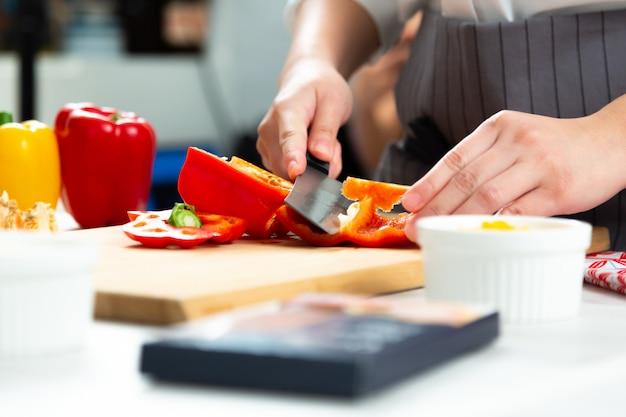 Шеф-повар нарезает сладкий перец на плаху на кухне Premium Фотографии