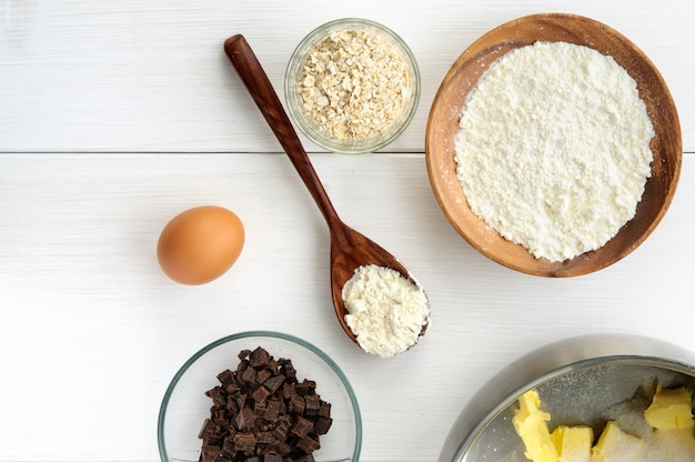 食材と白い木製の背景にオート麦クッキーを調理するための台所用品。平面図 Premium写真