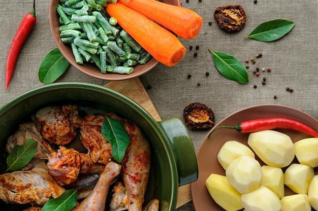 丸いセラミックシチュー鍋に野菜と鶏肉の平面図 Premium写真