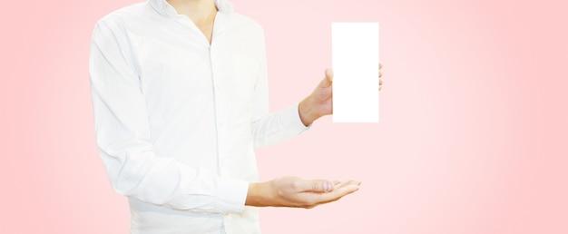 空白のパンフレットチラシを手で押し、白いシャツの男。 Premium写真