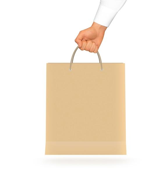 空白の黄色い紙袋を手に持ってモックアップします。 Premium写真