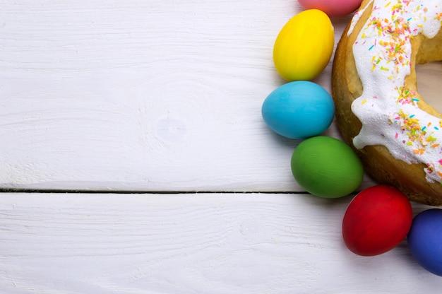 Пасхальные яйца и кулич на белой деревянной поверхности Premium Фотографии