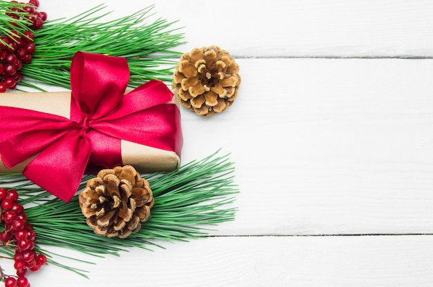 白い木製ヴィンテージ表面上のコーンと赤いリボン弓と枝クリスマスツリーとギフトボックス Premium写真