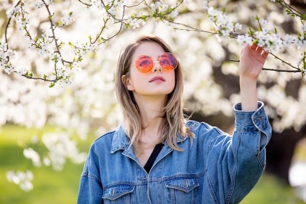 Молодая девушка в джинсовой куртке и солнцезащитных очках стоит возле цветущего дерева Premium Фотографии