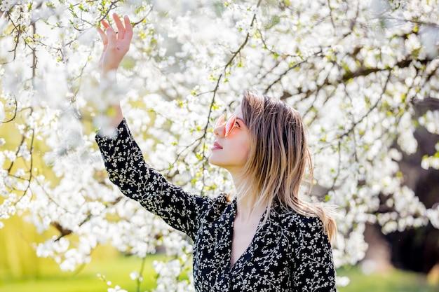 Молодая девушка в солнечных очках возле цветущего дерева Premium Фотографии