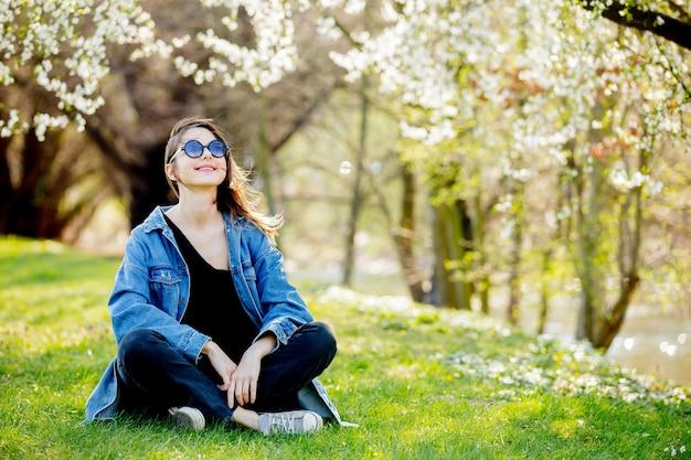Молодая девушка в джинсовой куртке и солнцезащитные очки, сидя возле цветущего дерева Premium Фотографии