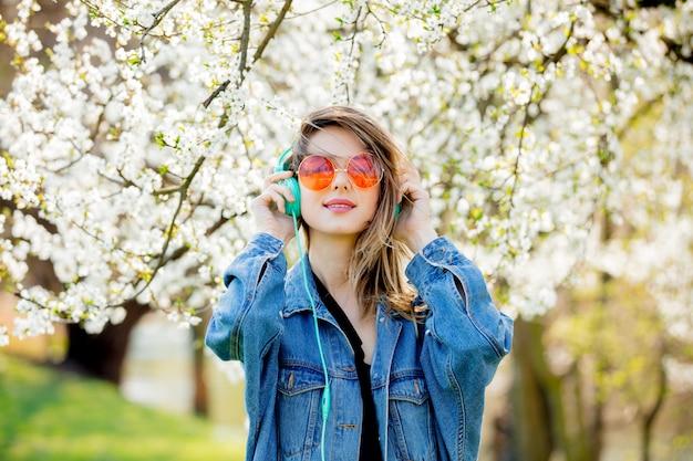 Девушка в джинсовой куртке и наушниках возле цветущего дерева Premium Фотографии