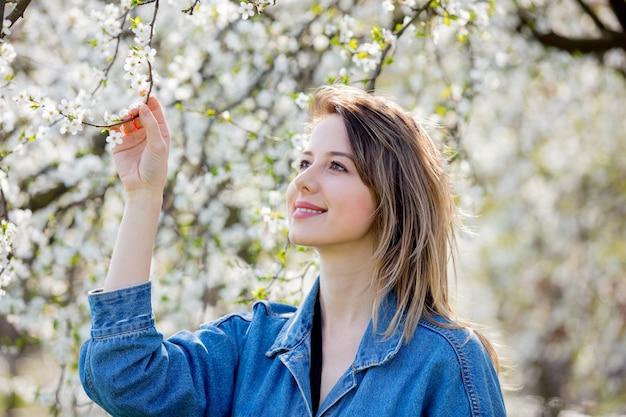 Девушка в джинсовой куртке возле цветущего дерева Premium Фотографии
